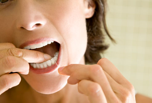 getty_rf_photo_of_woman_flossing_teeth