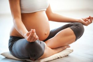 Close-up of pregnant woman meditating while sitting in lotus position